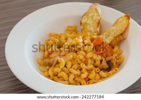 Italian tomato pasta served with garlic bread - stock photo