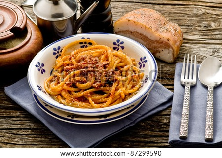 italian traditional pasta amatriciana served ona table wood - stock photo