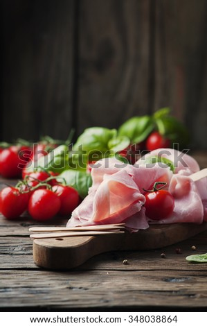 Italian traditional prosciutto with tomato and basil on the wooden table, selective focus - stock photo