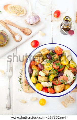 Italian traditional salad panzanella with fresh tomatoes and bread in a enamel bowl on a white wooden background - stock photo