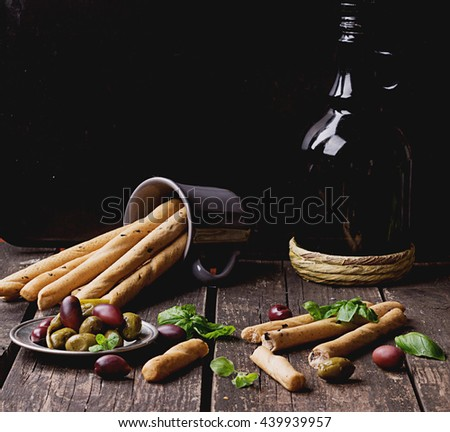 Italian Traditional Snack Grissini with green and black kalamata olives, olive oil and basil on the dark rustic wooden board