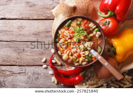 Italian vegetable minestrone soup in a bowl and ingredients on the table. horizontal view from above  - stock photo