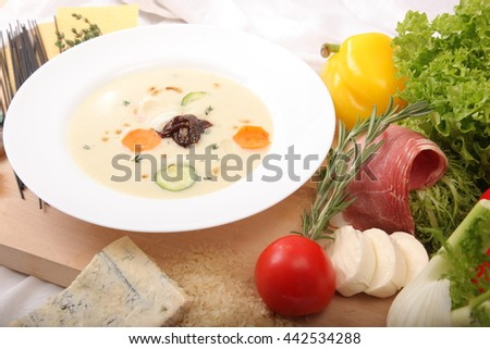 Italian vegetable soup, surrounded by fresh food on wooden board