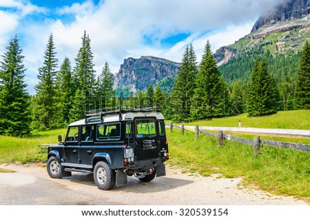 ITALY, CORTINA D'AMPEZZO- JULY 24, 2014: Jeep against amazing mountain peaks, the Alps, Italy