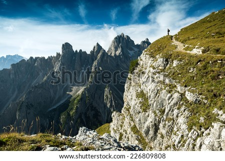 Italy, Dolomites - Man hiker standing very far from the edge of the barren rocks  - stock photo
