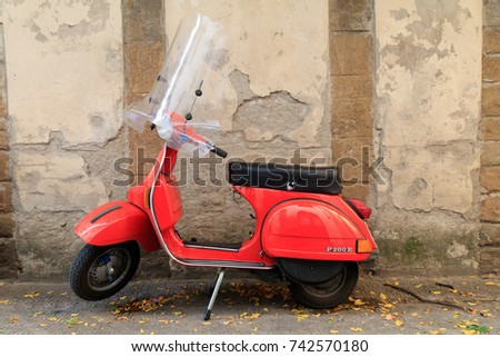 Italy. Florence. deteriorating stone wall and red Vespa P200E scooter. 2016-11-03