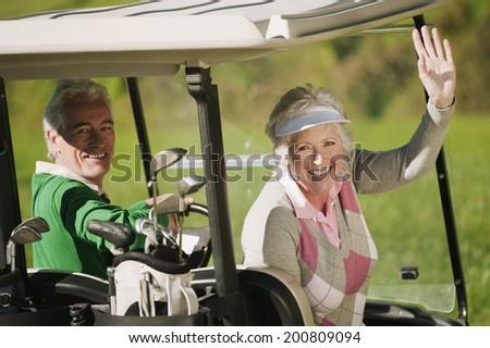 Italy, Kastelruth, Mature couple in golf cart - stock photo