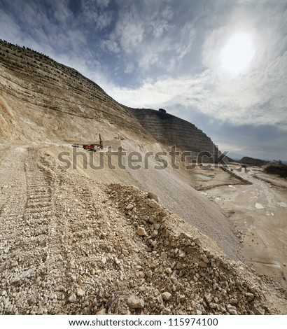 Italy, Maddaloni (Naples), stone pit with industrial vehicles at work - stock photo