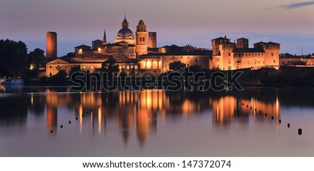italy mantua duke palace and castle panoramic view at sunset with reflection in lake water illuminated landmark