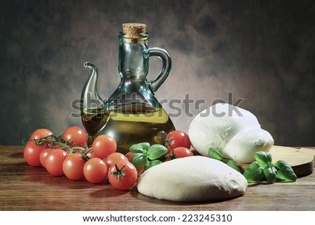 Italy, olive oil, basil, tomatoes, mozzarella cheese, dough; ingredients for italian Pizza on a wooden table - stock photo