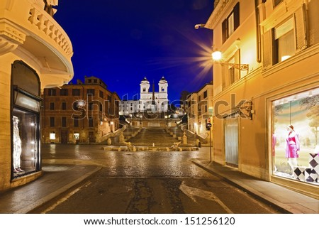 Italy rome spanish stairs at sunrise with landmark fountain and church ancient city shopping street with display windows of fashion stores - stock photo