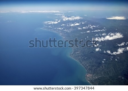 Italy, Sicily, aerial view of the sicilian countryside and the Tyrrhenian Sea coastline (volcano Etna in the background) - stock photo