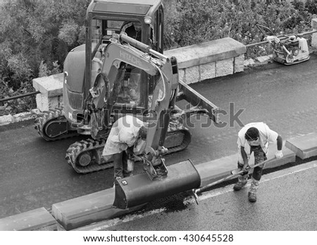 Italy, Sicily; 1 June 2016, men at work fixing a road - EDITORIAL
