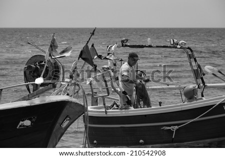 Italy, Sicily, Mediterranean sea, Sampieri (Ragusa Province), fisherman working ashore on his fishing boat