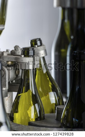 Italy, Sicily, wine bottles being washed and filled with wine by an industrial machine in a wine factory