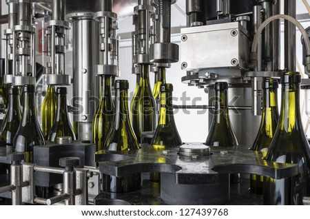 Italy, Sicily, wine bottles filled with wine by an industrial machine in a wine factory - stock photo