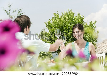 Italy South Tyrol couple in restaurant toasting with white wine smiling