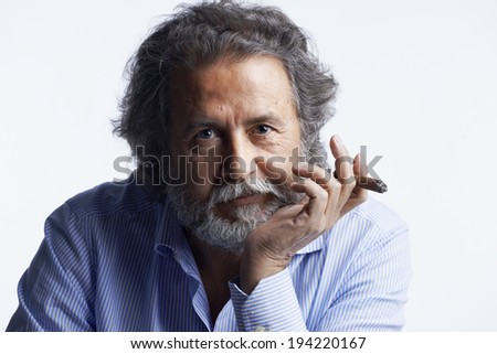 Italy, studio portrait of a bearded middle aged man with a cigar