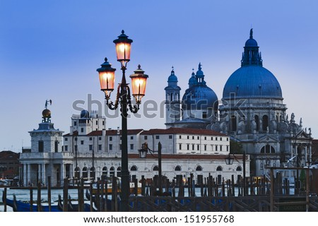 Italy Venice island city at sunset view over gondola poles to Santa Maria della salute cathedral over canal illuminated murano glass lamp - stock photo