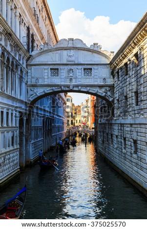 ITALY, VENICE - JUN 1 2014: Gondolier on  gondola on the Bridge of Sight  taking tourist for a ride. Venice. Gondola's are a major mode of touristic transport in Venice, Italy .  - stock photo