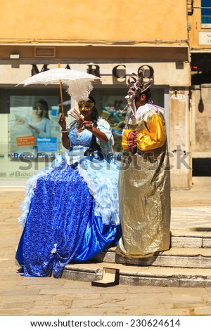 ITALY VENICE-JUN 1 2014: Persons attends in costumes and golden masks,  standing in front of a church entry during traditional carnival in Venice. This attraction brings many tourist to visit Venice - stock photo