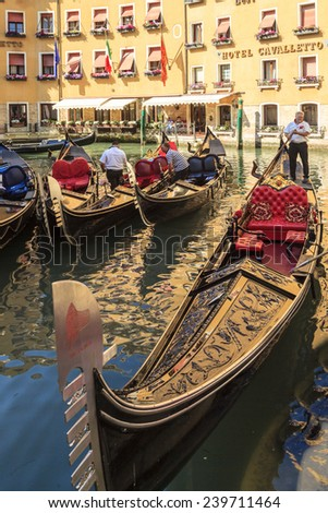 ITALY, VENICE - JUNE 1 2014: Gondoliers are awaiting for tourists to take a ride. Venice. Gondola's are a major mode of transport in Venice . More than 20 million tourists come to Venice annually. - stock photo