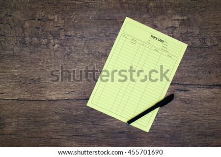 Item inventory stock list card with black pen over wooden background - stock photo