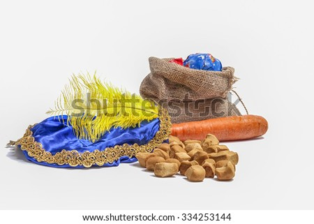 Items concerning the Dutch holiday of Sinterklaas. Carrot for the horse, sweets, bag with presents and the hat of Zwarte Piet - stock photo