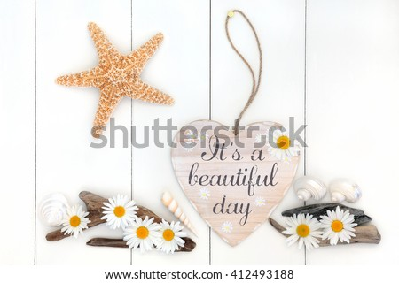 Its a beautiful day distressed heart shaped sign with daisy flowers, driftwood,  starfish and sea shells over white wooden background. - stock photo