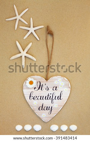 Its a beautiful day distressed wooden sign with starfish and cockle shells on beach sand background. - stock photo