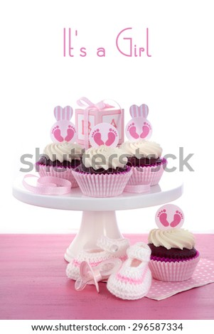 Its a Girl Baby Shower Cupcakes with baby feet toppers and decorations on shabby chic pink wood table.  - stock photo