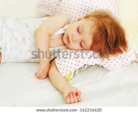 ittle baby asleep in bed, his head on the pillow close-up. - stock photo