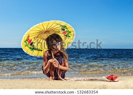ittle girl on a beautiful day at the beach playing with her crab pet