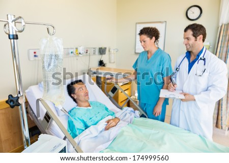 IV bag hanging on rod with medical team looking at patient in hospital room - stock photo