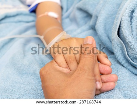 IV solution in a child's patients hand  - stock photo