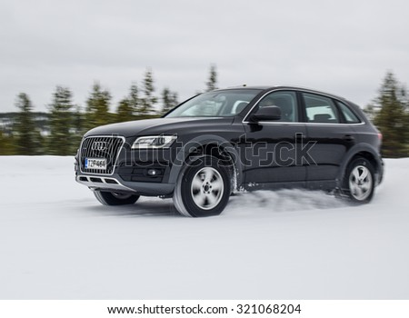 IVALO, FINLAND - February 15, 2015: Winter tire test is held at the proving ground. Test-driver performs acceleration on snow test to determine the tire which provides the best grip on snow.