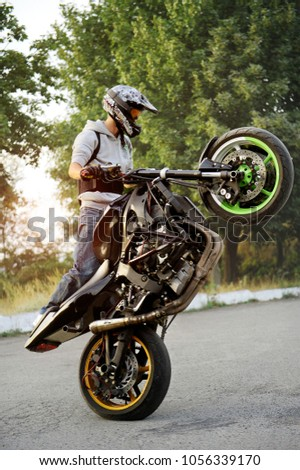 Ivano-Frankivsk, Ukraine - 28 August 2015 : Good photo of a stuntman doing trick riding motorcycle on one cycle along the street. Green tricks on background. Summer sunset.