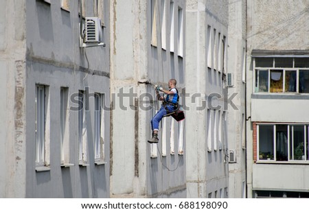Ivanovo, Russia. - July 29, 2017: Industrial climber. Repair of the facade of the building.