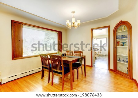 Ivory dining room with wooden dining table set, shiny hardwood floor and built-in cabinet with glass door