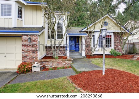 Ivory house with red brick wall trim. View of entrance porch and front yard landscape - stock photo