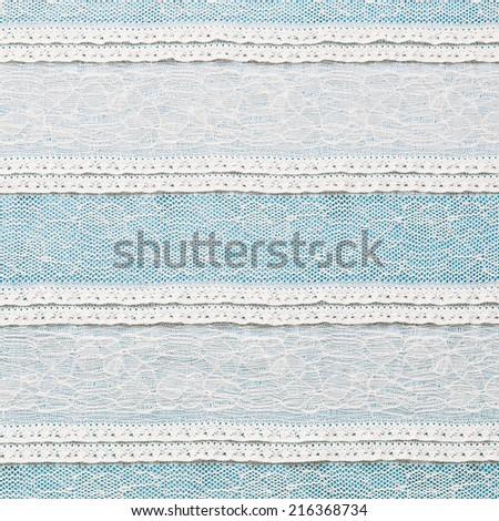 Ivory lace fabric on blue background - stock photo