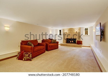 Ivory living rom with granite tile background fireplace and red comfortable armchairs - stock photo
