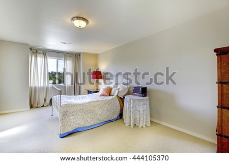 Ivory wall bedroom with white iron bed and red lamp on the nightstand. Also beige carpet floor.