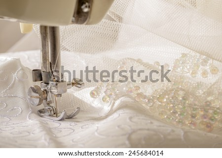 Ivory wedding dress fabric being sewn on vintage machine - stock photo