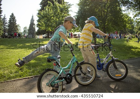 IZHEVSK, RUSSIA - JUNE 12, 2016 : Two children start to ride bicycles.