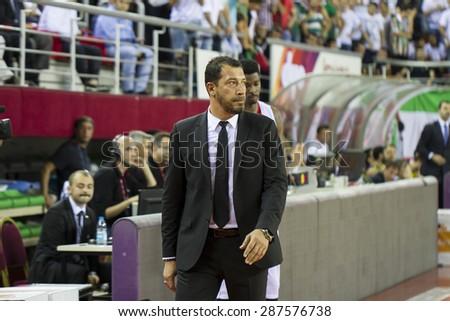 IZMIR - JUNE 06: Pinar Karsiyaka's Coach UFUK SARICA standing near the bench in Turkish Basketball League game between Pinar Karsiyaka 82-64 Fenerbahce Ulker on June 06, 2015 in Izmir - stock photo