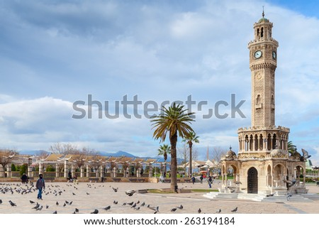 Izmir, Turkey - February 12, 2015: Doves and walking ordinary people on Konak Square near the historical clock tower - stock photo