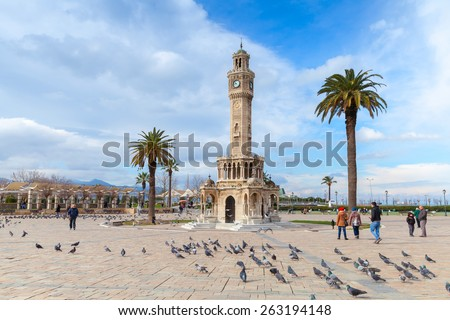 Izmir, Turkey - February 12, 2015: Doves and walking people on Konak Square near the historical clock tower - stock photo