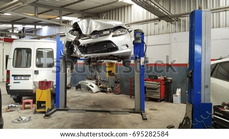 IZMIR ,TURKEY - JULY 14, 2017: Crashed Grey Ford Fiesta Car at Service waiting on lift for repair.