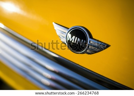 Izmir, Turkey - March 19, 2015: Photo of a Mini Cooper car logo badge on a yellow Mini Cooper car. - stock photo